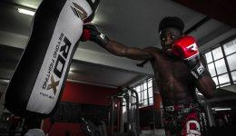 man working with punching bag at gym